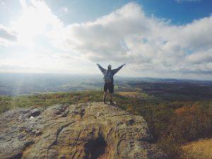 山頂で両手を掲げて達成感を感じる男性